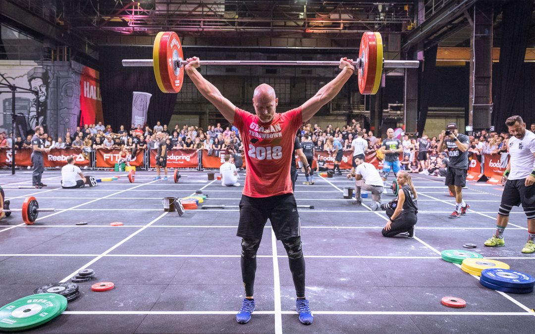 Master Athlet steht in der Endposition des Snatches